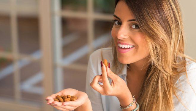 Frau isst Mandeln von nussundgenuss